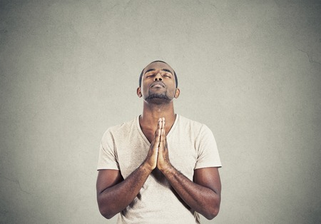 believe: Closeup portrait young man praying hands clasped hoping for best asking for forgiveness or miracle isolated gray wall background. Human emotion facial expression feeling