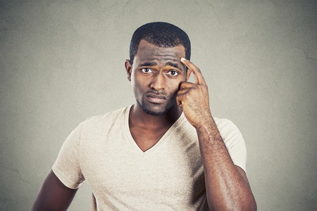 scratching head: Preoccupied man scratching his head looking for solution