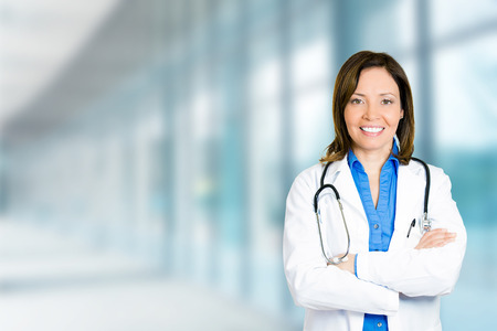 one female: Portrait confident mature female doctor medical professional standing isolated on hospital clinic hallway windows background. Positive face expression Stock Photo