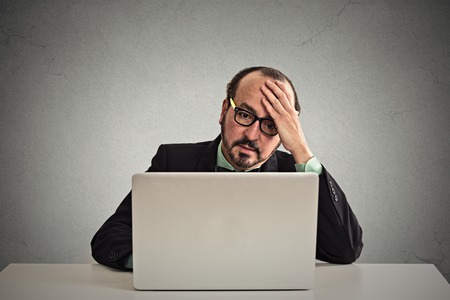 computer problem: Portrait mature stressed displeased worried business man sitting in front of laptop computer isolated on gray office wall background. Negative face expression emotion feelings problem perception
