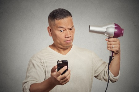 thinning: Closeup portrait surprised skeptical man reading social media news on smartphone looking at mobile phone holding hairdryer isolated on grey wall background. Human face expression. Mind blowing deal