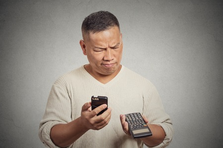 Confused man looking at his smart phone holding calculator isolated on gray wall background photo