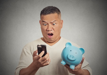 shock: Portrait shocked man looking at his smart phone holding piggy bank