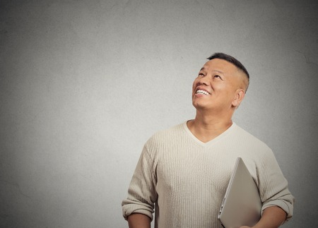 deciding: Portrait happy man thinking looking up isolated on grey wall background with copy space. Human face expressions, emotions, feelings, body language