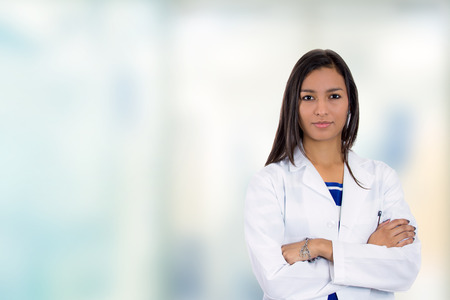Portrait confident young female doctor medical professional standing in corridor isolated on hospital clinic hallway windows background. Positive face expression Stock Photo
