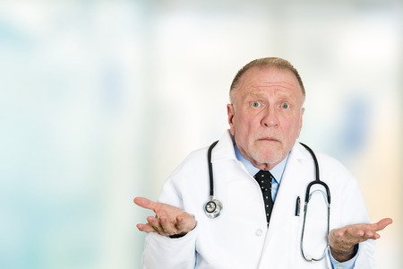 Closeup portrait clueless senior health care professional doctor with stethoscope, has no answer, doesn't know right diagnosis standing in hospital hallway isolated clinic office windows background. Banque d'images