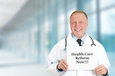 reform: Senior happy doctor holding health care reform now sign standing in hospital hallway background with clinic office windows