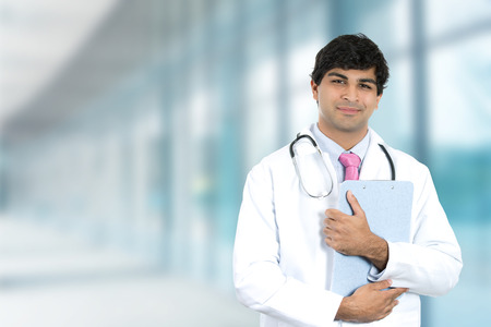 Portrait of friendly smiling male doctor with clipboard standing in hospital hallway clinic isolated on office windows background Standard-Bild