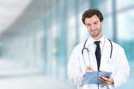 Portrait of friendly male doctor with clipboard smiling standing in hospital hallway clinic office windows background photo