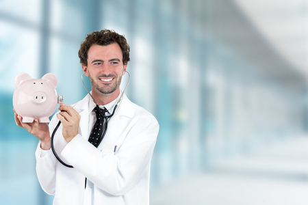 Portrait happy smiling doctor holding listening to piggy bank with stethoscope standing in hospital hallway on clinic office windows background photo