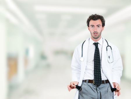 Stressed young doctor penniless showing empty pockets standing in hospital hallway clinic office background