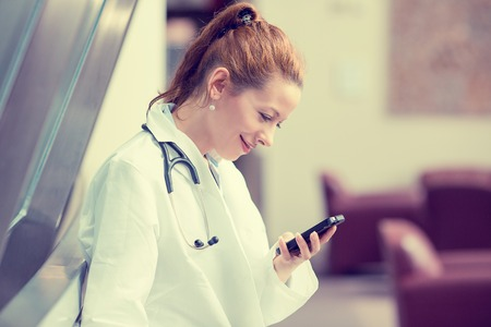 Side profile portrait smiling female doctor, healthcare professional in white lab coat with stethoscope, analyzing data results on mobile smart phone standing in hospital hallway corridor Foto de archivo