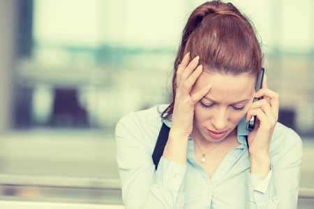 servicio al cliente: Retrato infeliz mujer joven hablando por teléfono móvil mirando hacia abajo. Expresión del rostro humano, la emoción, la reacción de malas noticias Foto de archivo