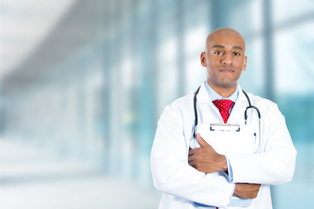 Portrait happy confident young doctor standing in hospital hallway corridor on a background of clinic windows photo