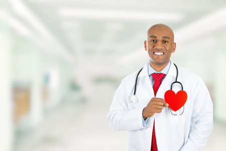 internal medicine: Happy smiling doctor holding red heart standing in hospital hallway on clinic office background. Cardiology care appointment annual check up concept