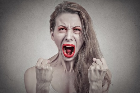 feeling up: Screaming girl. Closeup portrait angry young woman hysterical having nervous breakdown fists up in air isolated on grey wall background. Negative human emotion facial expression feeling Stock Photo