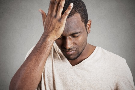 Closeup headshot very sad depressed, stressed, alone, disappointed gloomy young man head on hands having suicidal thoughts isolated grey wall background. Human emotion facial expression reaction Stockfoto