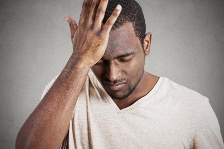 avergonzado: Headshot del primer muy triste deprimido estresado, sombrío cabeza, solo, decepcionado joven en las manos que tienen pensamientos suicidas aislado fondo de la pared gris. La emoción humana reacción expresión facial