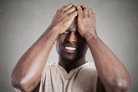 decepcionado: Headshot del primer muy triste deprimido estresado, sombrío cabeza, solo, decepcionado joven en las manos que tienen pensamientos suicidas aislado fondo de la pared gris. La emoción humana reacción expresión facial