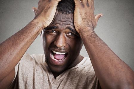 Close-up headshot erg verdrietig depressief, benadrukte teleurgesteld sombere jongeman hoofd op handen huilen schreeuwen in wanhoop op een grijze muur achtergrond. Menselijke emotie gezichtsuitdrukking reactie