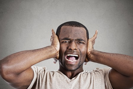 isolated on gray: Closeup portrait upset stressed young man squeezing his head, going nuts, screaming, losing mind, isolated gray wall background. Negative emotion feeling reaction
