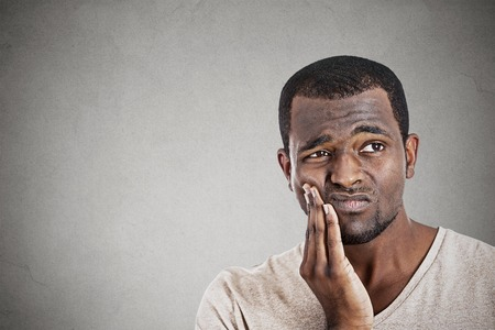 grimace: Closeup portrait handsome young man touching face having really bad pain tooth ache isolated gray wall background. Negative human emotions, facial expression feelings
