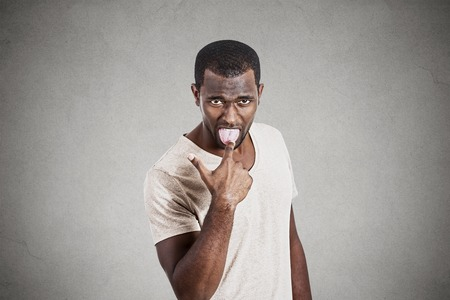 Young angry, unhappy man with finger in mouth something sucks gesture isolated on gray background. Negative facial emotions, expressions, feelings