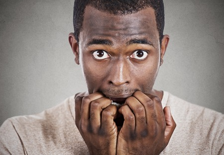 obsessive compulsive: Headshot young anxious man biting fingernails looking at you camera isolated on gray wall background. Human face expressions, emotions, feelings Stock Photo