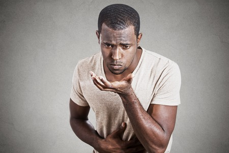 throw up: Closeup portrait young unhappy sick man about to chuck, throw up, retch barf isolated on gray wall background. Negative human emotion feeling facial expressions. Excessive drinking Stock Photo