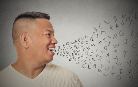 verbal: Side view portrait young handsome man talking with alphabet letters coming out of open mouth isolated grey wall background. Human face expression emotion perception. Communication concept