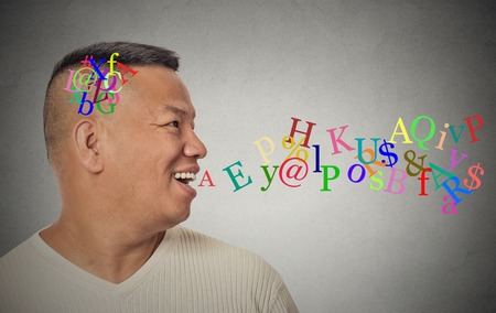 nonsense: Side view portrait young handsome man talking with alphabet letters coming out of open mouth isolated grey wall background. Human face expression emotion perception. Communication concept