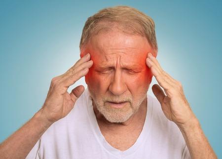 dolor de cabeza: Primer hombre mayor tiro en la cabeza que sufren de dolor de cabeza las manos en la cabeza con las áreas inflamadas de color rojo mirando hacia abajo aislado en fondo azul claro. Expresión de la cara humana. Problemas de salud temas Foto de archivo