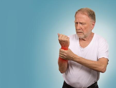 Souffrant de douleurs et rhumatismes. Gros plan personnes âgées, senior vieil homme regardant misérable en grande atroce mal de main douloureuse poignet coloré en rouge isolé sur fond bleu. Questions de santé problèmes