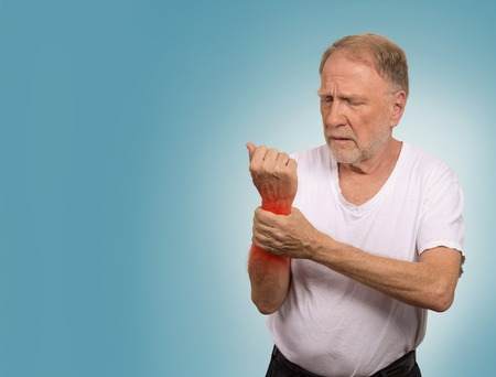 wrist pain: Suffering from pain and rheumatism. Closeup elderly, senior old man looking miserable in great excruciating hand ache painful wrist colored in red isolated on blue background. Health issues problems