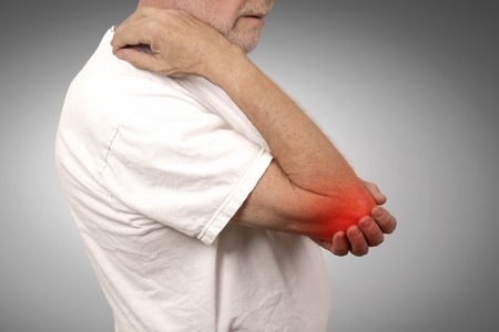 Closeup senior man with elbow inflammation colored in red suffering from pain and rheumatism isolated on gray wall background Stockfoto