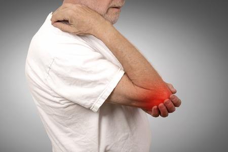 Hombre mayor del primer con la inflamación del codo de color rojo en el sufrimiento del dolor y el reumatismo aislado sobre fondo gris de la pared