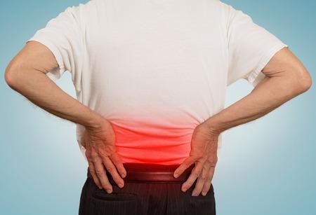 uomo rosso: vista posteriore vecchio nonno che tiene il suo doloroso inferiore della schiena colorato in rosso con le mani isolato su sfondo azzurro. Problemi di salute umana Archivio Fotografico