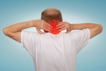 spondylitis: Closeup senior mature man with bad neck spasm pain touching colored in red inflamed area suffering from arthritis isolated on light blue background. Human health problems, geriatrics medicine concept