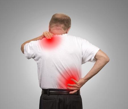columna vertebral: Hombre de edad mayor con el dolor de espalda inferior y superior aislado en el fondo de la pared gris. Problemas de la m�dula espinal