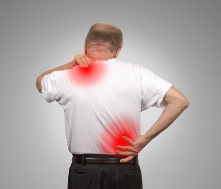 chiropractic: Senior elderly man with lower and upper back pain isolated on gray wall background. Spinal cord problems Stock Photo