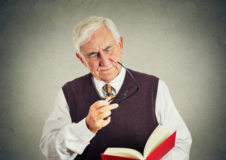 isolated on gray: Closeup portrait senior elderly man holding book, glasses having eyesight problems unable to read isolated gray wall background. Human emotion facial expressions. Age related changes