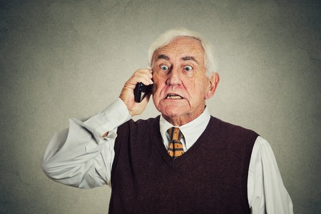 Angry senior man talking on mobile phone isolated on gray wall background. negative emotions