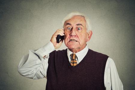 hombre viejo: Hombre mayor enojado hablando por tel�fono m�vil aislado en el fondo de la pared gris. emociones negativas