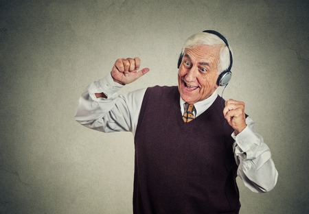 Closeup portrait elderly man, senior retired guy with headphones listening to the radio, enjoying music and his life isolated on gray wall background. Positive human emotions, face expression