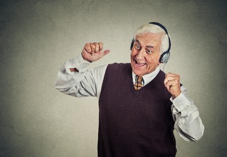oir: Retrato del primer anciano, hombre jubilado con auriculares escuchando la radio, disfrutando de la música y su vida aislada en el fondo de la pared gris. Emociones humanas positivas, expresión de la cara