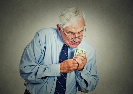 Closeup portrait greedy senior executive, CEO, boss, old corporate employee, mature man, holding dollar banknotes isolated on gray wall background. Negative human emotion facial expression Archivio Fotografico