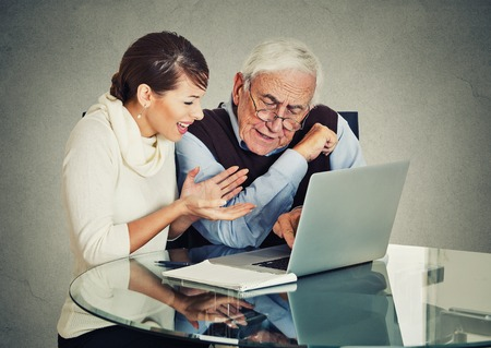 generation gap: Young woman teaching confused, senior, older, elderly man with eyeglasses how to use laptop. Generation gap differences concept