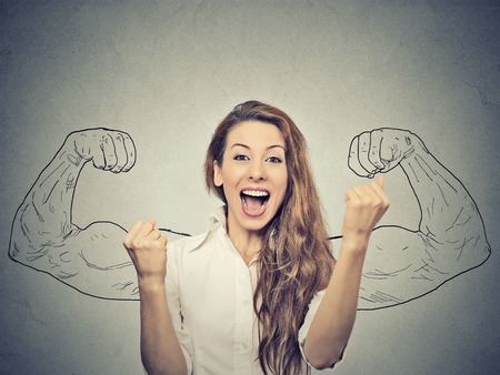 happy woman exults pumping fists ecstatic celebrates success on gray wall background Standard-Bild