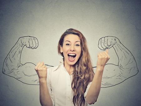 celebra: mujer feliz se regocija puños de bombeo extática celebra éxito en el fondo gris de la pared Foto de archivo