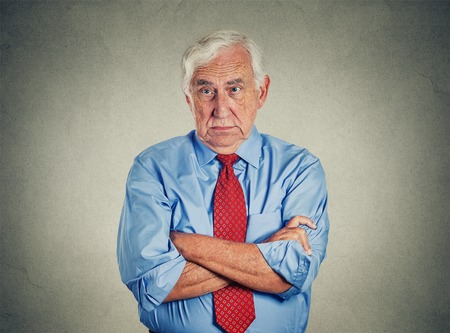 bad leadership: Portrait of unhappy grumpy pissed off senior mature man isolated on gray wall background. Negative human emotions, face expression feelings